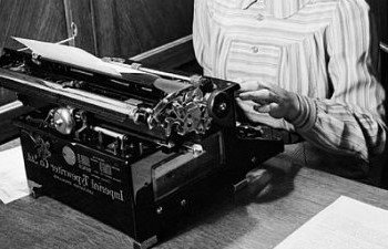 A vintage photograph of someone typing at a typewriter